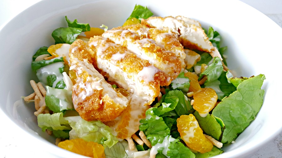 chicken oriental salad topped with dressing in a bowl