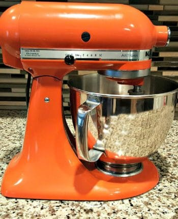 A KitchenAid Artisan Series 5-Qt. Stand Mixer with Pouring Shield on a counter top