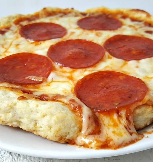 small cooked pizza for one sitting on a plate