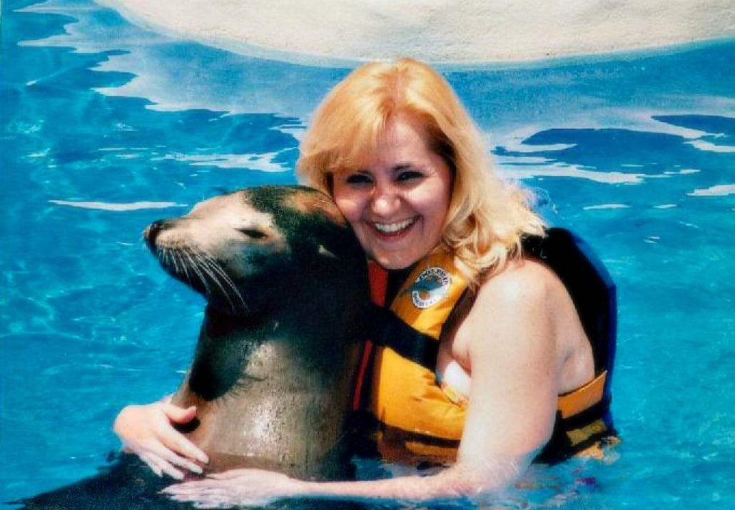 a woman wearing a life jacket hugging a sea lion in water