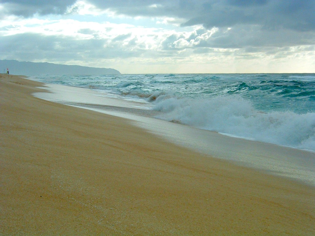 a sandy beach with waves crashing on the shore and a mountain in the distance