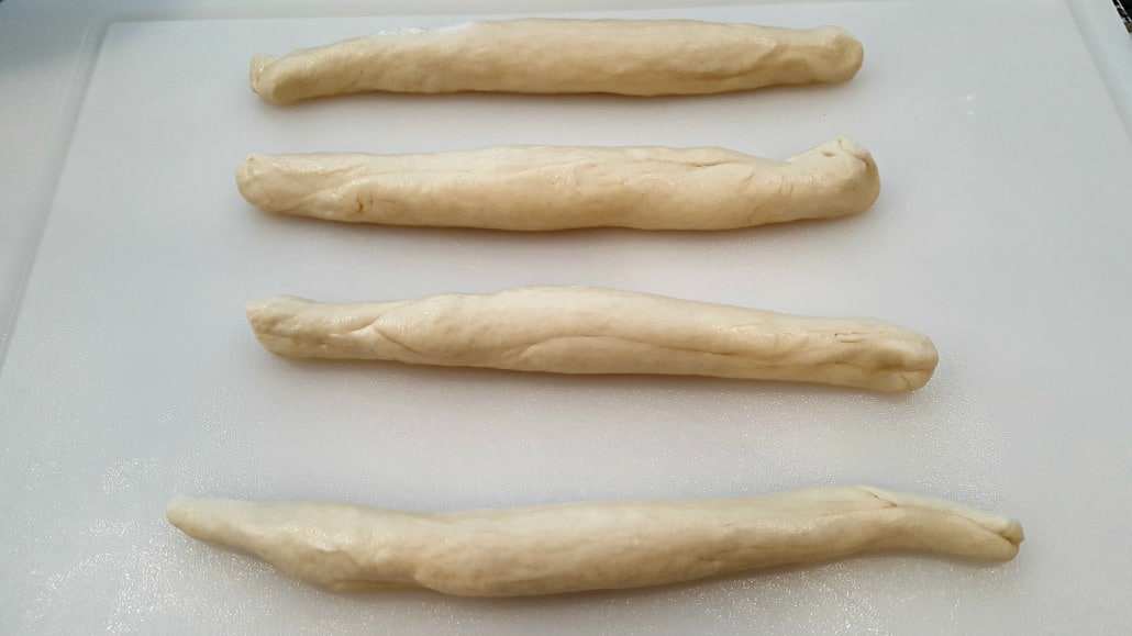 four pieces of dough rolled into log shapes