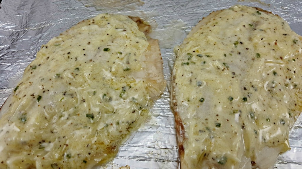cheese mixture spread on Tilapia fillets on a tinfoil lined baking sheet