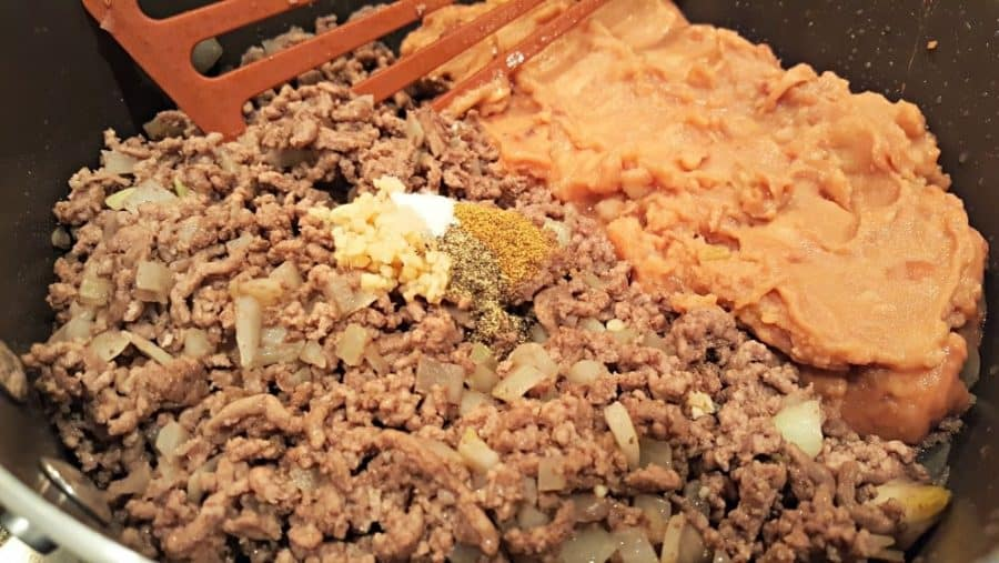 ground beef and onion with refried beans and seasonings