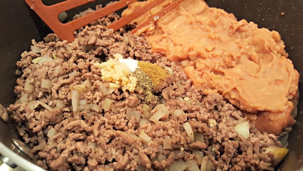 ground beef, refried beans and seasonings frying in a pan