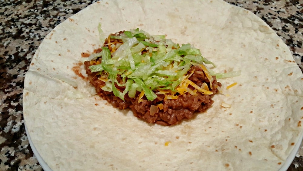 a burrito tortilla on a plate topped with ground beef mixture, cheese, and lettuce