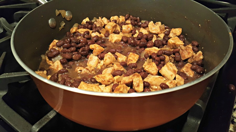 adding black beans to sauted chicken in frying pan
