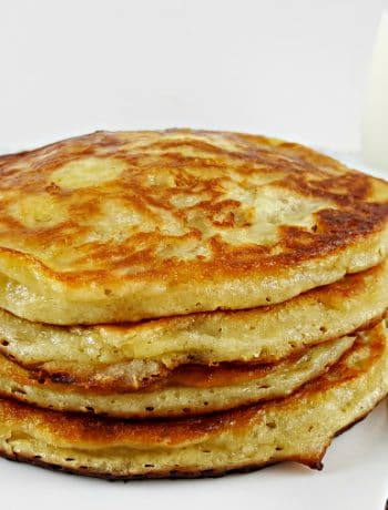 four pancakes stacked on a plate with a fork and a glass of milk