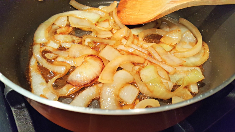 caramelized onions cooking in a pan with a wooden spoon