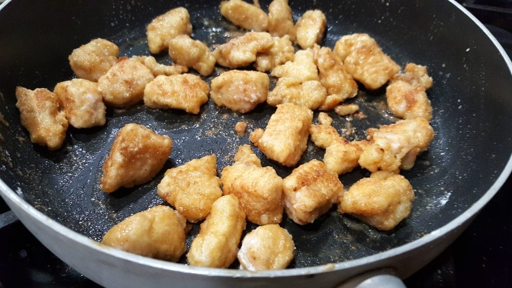 breaded chicken cooking in a frying pan