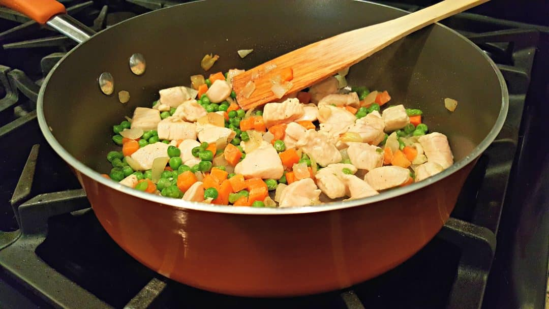 peas, carrots, onions, and chicken cooking in a pan