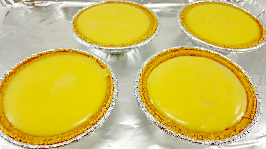 four unbaked mini key lime pies on a baking sheet