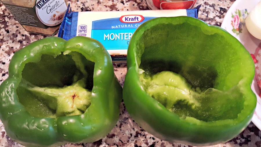 two green peppers with tops cut off and seeds removed, block of cheese, jar of garlic on the side