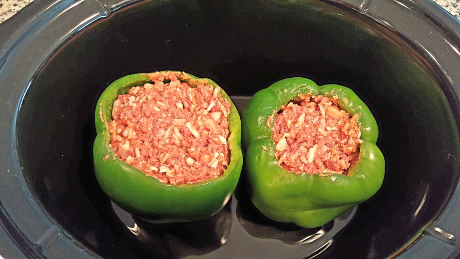 two green peppers stuffed with ground beef mixture inside a crockpot