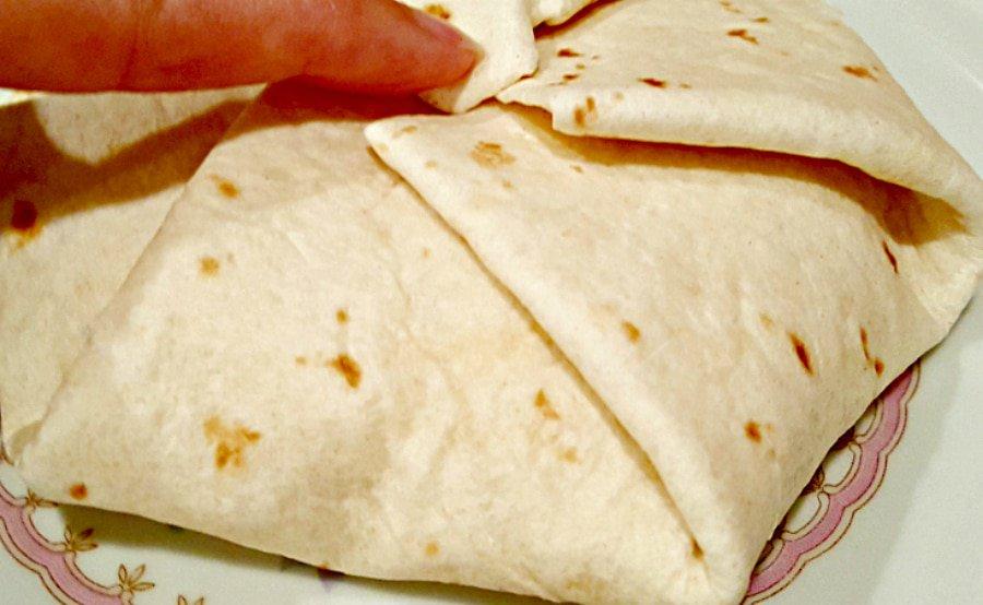 a finger folding the tortilla edges in toward the center