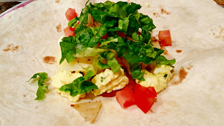 bacon, egg, cheese, onion, tomato, and lettuce on a tortilla