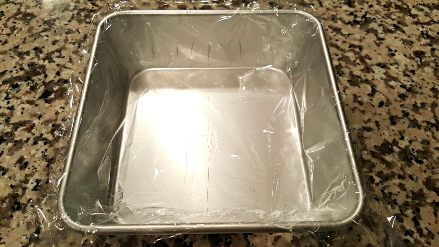 cake pan lined with plastic wrap