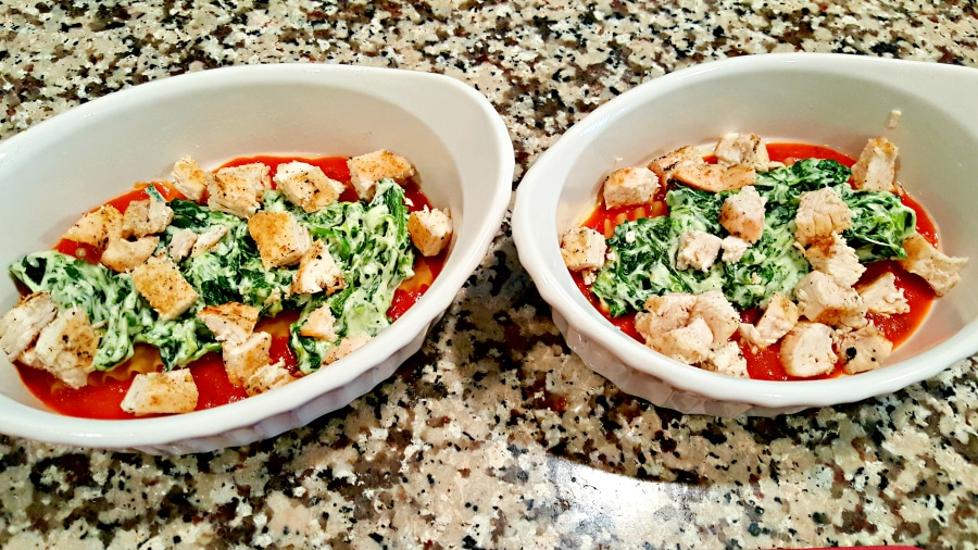 two baking dishes with chicken on top of spinach mixture