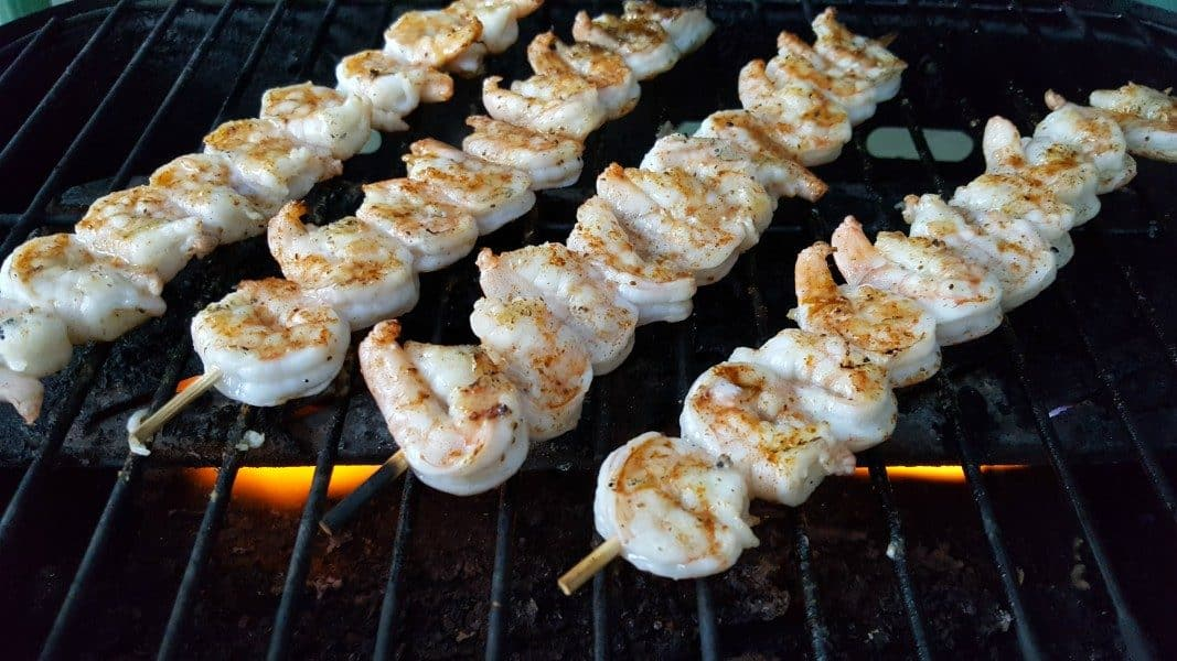 four skewers of shrimp cooking on a gas grill