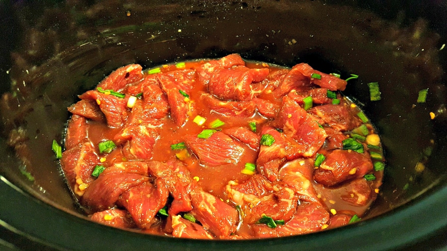 beef, sauce, and green onions in a slow cooker