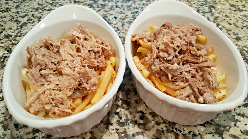 two baking dishes filled with fries and shredded pork