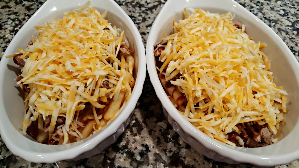 two baking dishes filled with bbq pork fries topped with cheese