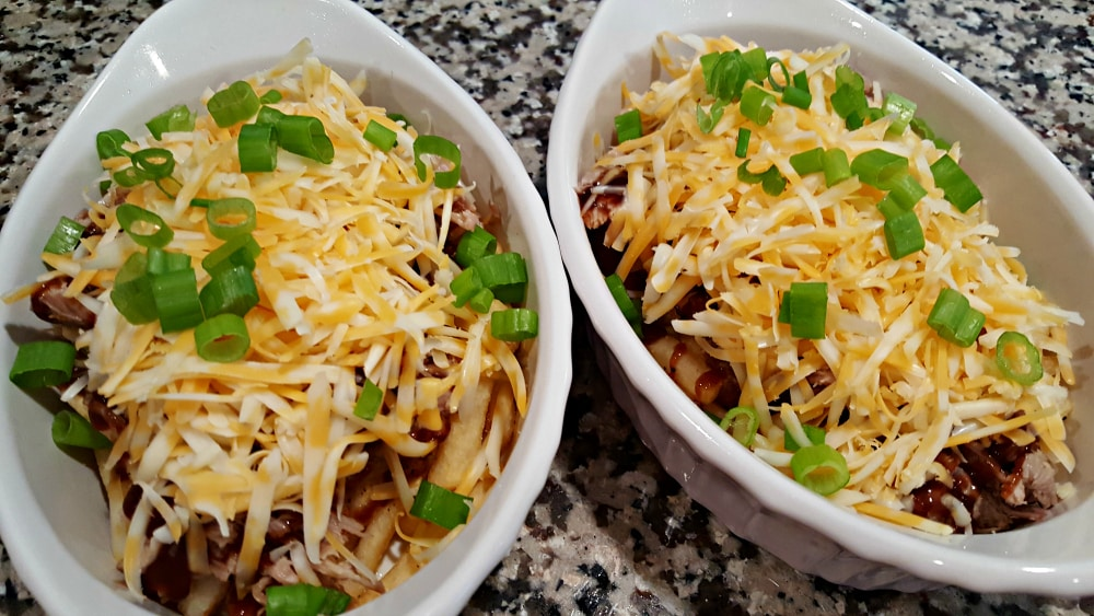 two baking dishes filled with fries, pork, bbq sauce, shredded cheese and topped with green onion