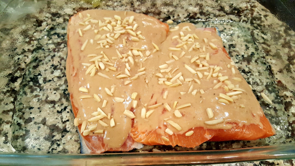 two salmon filets in a baking dish topped with sauce and almonds