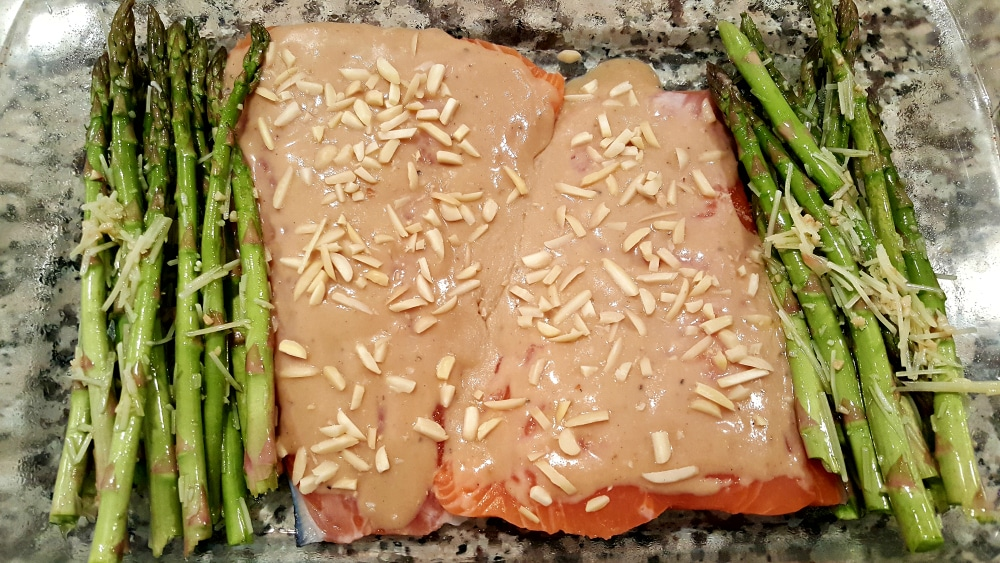 two sauce and almond covered salmon filets in a baking dish with asparagus