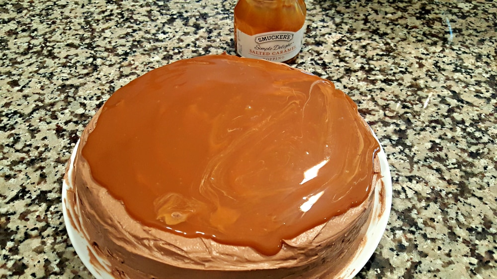 a round cake with brown frosting topped with salted caramel