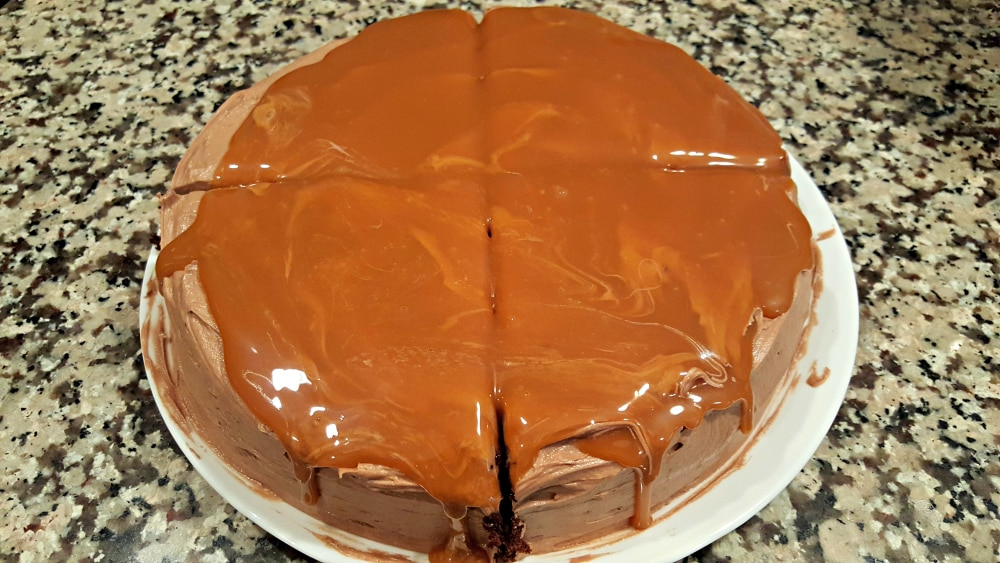 a round cake with brown frosting and salted caramel topping cut into four wedges