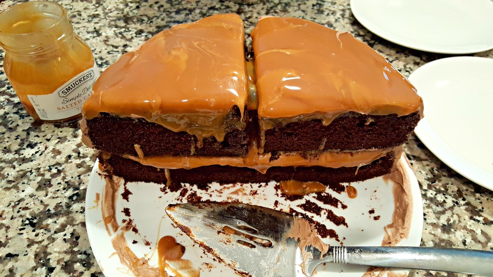 two pieces of two layer chocolate cake with caramel topping on a plate with a pie server