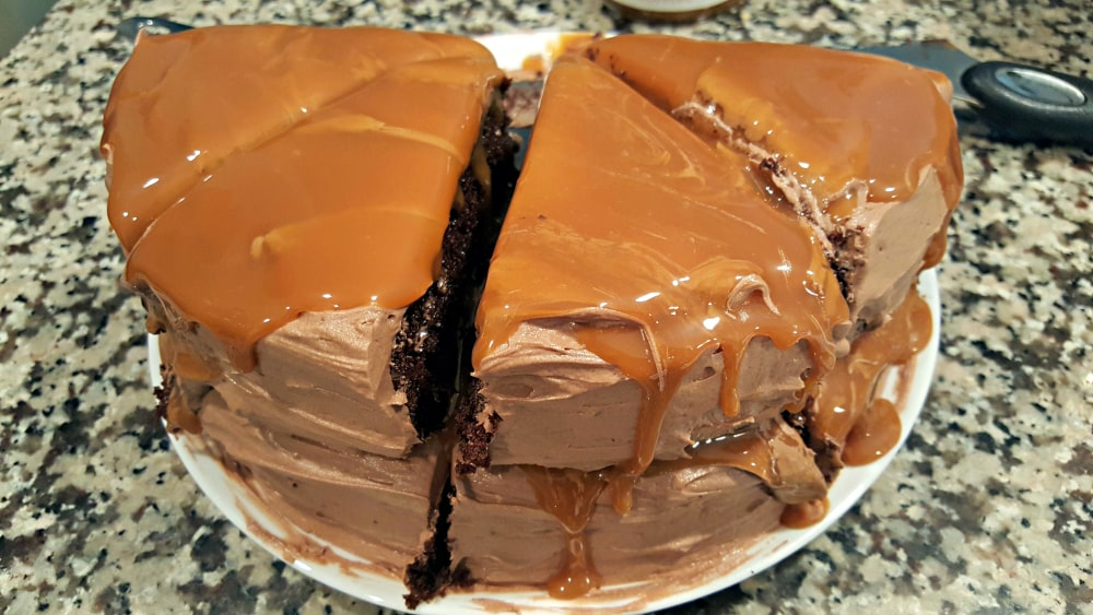 four pieces of two layer chocolate cake and caramel topping on a plate