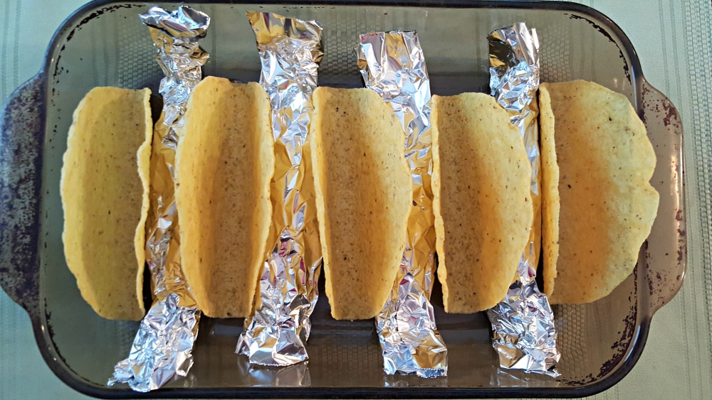 4 rolls of tinfoil in a baking dish with 5 taco shells propped up between them