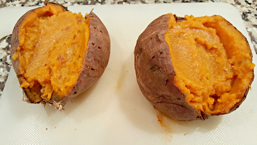 two sweet potatoes will filling mixture in them on a cutting board