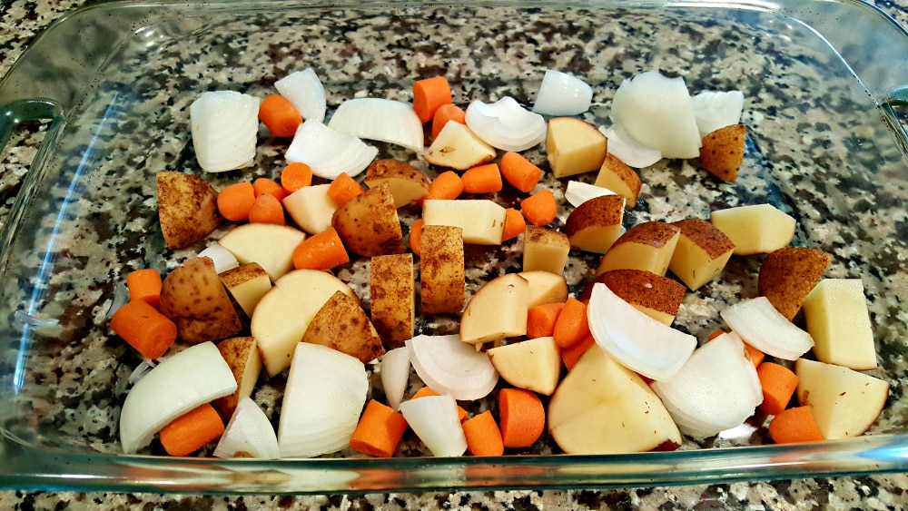 potatoes, carrots and onions in a glass baking dish