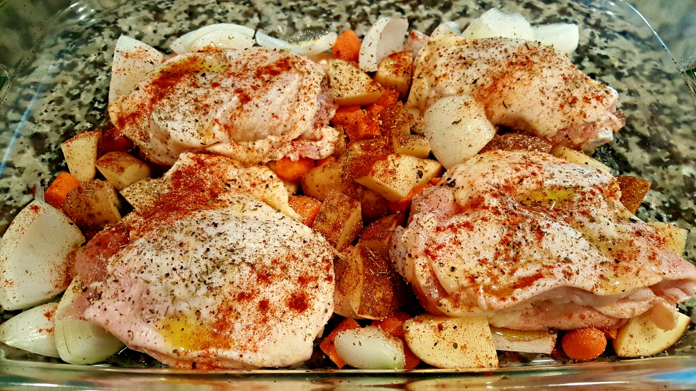 chicken and veggies in a baking dish and sprinkled with paprika, salt and pepper