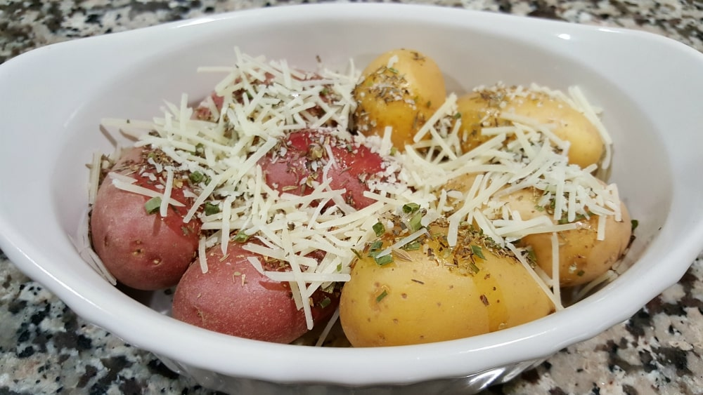 olive oil, garlic, thyme, oregano, basil, chives, onion flakes, and Parmesan sprinkled onto fingerling potatoes in a baking dish