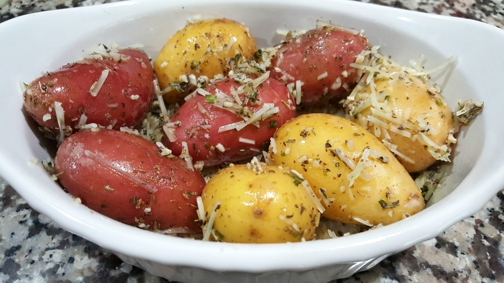 olive oil, garlic, thyme, oregano, basil, chives, onion flakes, and Parmesan mixed with fingerling potatoes in a baking dish