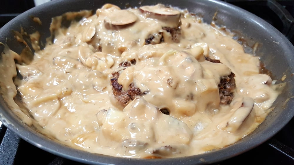 two salisbury beef patties cooking in a frying pan covered with mushroom sauce