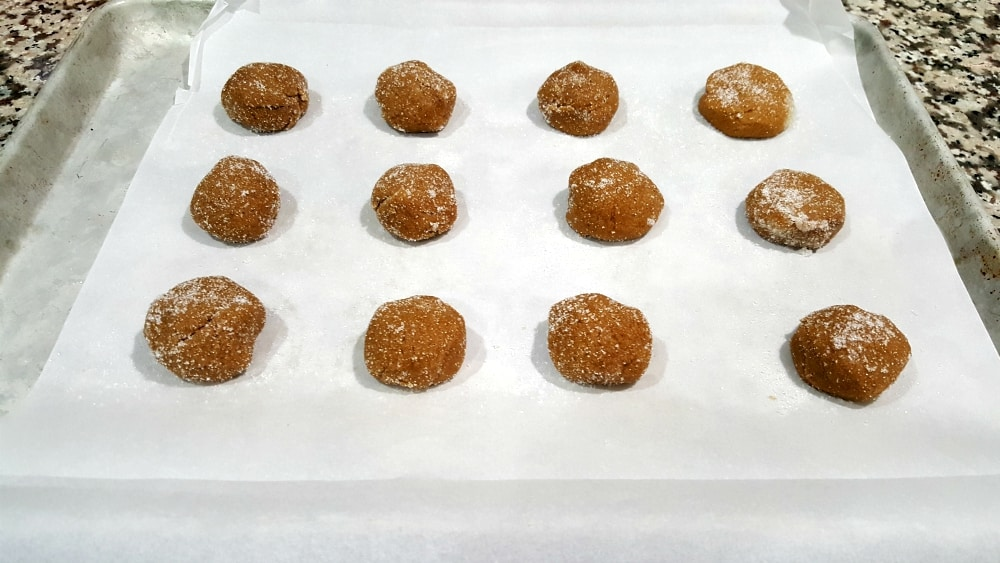 12 gingerbread sugary dough balls sitting on parchment paper on a baking tray