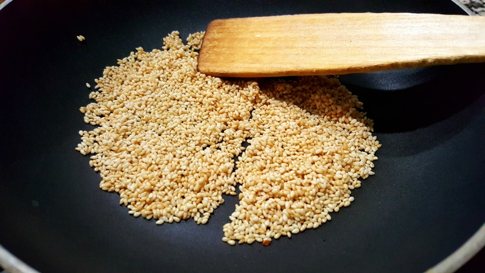 sesame seeds frying in a dry frying pan