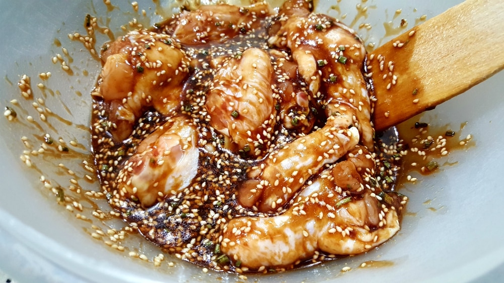 raw chicken wings in a bowl with hoisin sauce mixture and wooden spatula
