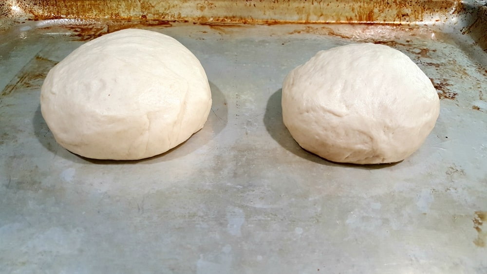 two balls of dough placed on a cookie sheet