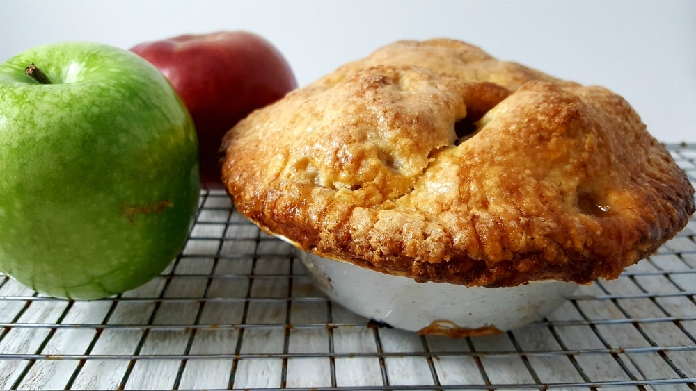 a baked golden brown pie on a wire rack with a green apple and red apple
