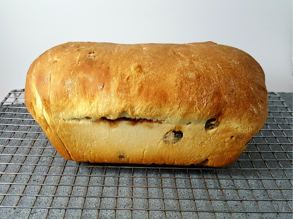 a baked loaf of raisin bread on a wire rack