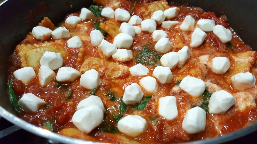 ravioli, diced tomatoes, spaghetti sauce, garlic, spinach, ricotta, and mozzarella cooking in a pan