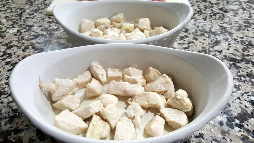 cooked diced chicken in two individual baking dishes