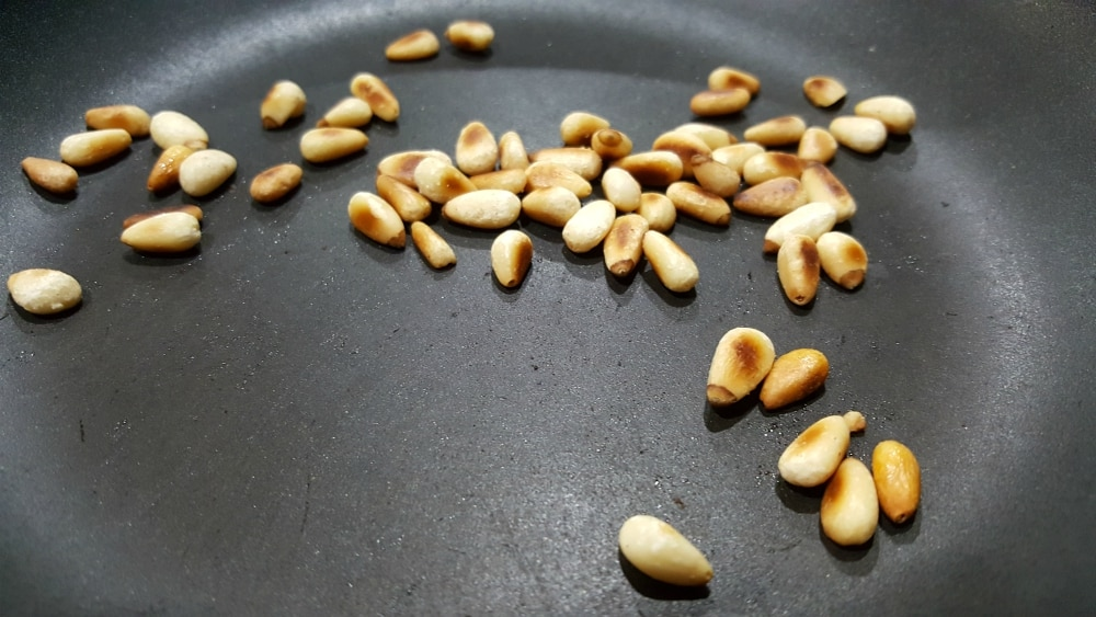 pine nuts cooking in a frying pan