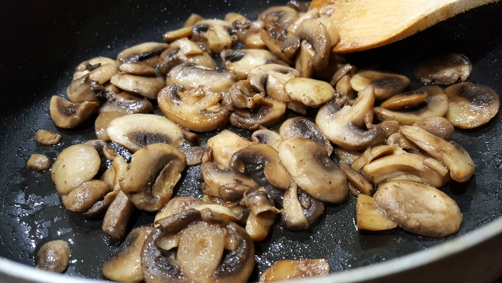 mushrooms and butter cooking in a frying pan
